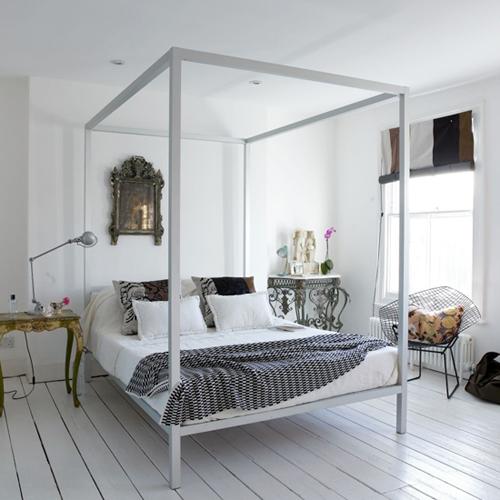 contemporary four poster bed is combined with antique finds and