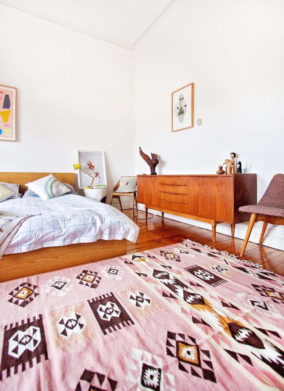 a bedroom with a soft pink kilim rug the style files