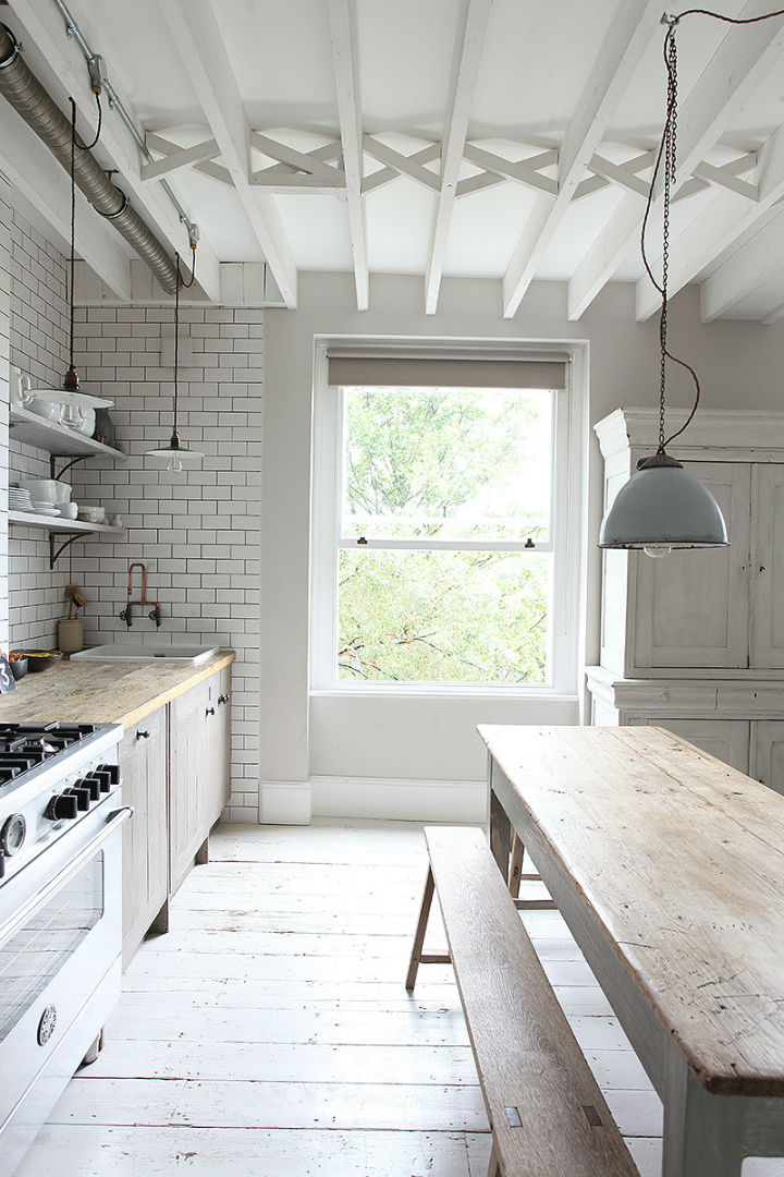 the distressed cabinets have a rustic feel but the clean rectangular tiles give the open plan space a modern edge it is a balance that works perfectly - Rustic Modern Kitchen